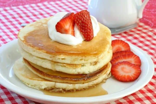 Fresh and homemade pancakes topped with cream and strawberries.